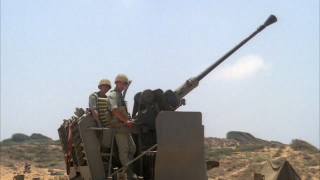 MEDIUM ANGLE OF SOLDIERS STANDING BEHIND AN ANTI AIRCRAFT GUN. SEE SOMEONE RUN ACROSS FOREGROUND. SEE SOLDIERS CONTROL GUN AS IT BEGINS TO FIRE SEVERAL TIMES AT SOMETHING OFF SCREEN. THEN SEE GUN LOWERED. SEE DESERT PLAINS AREA IN BACKGROUND. MIDDLE EAST.