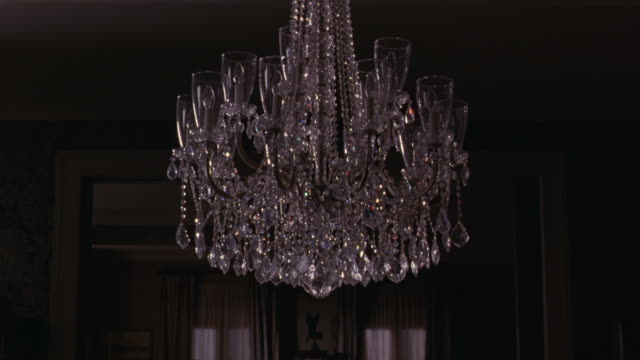 MEDIUM ANGLE OF  A CHANDELIER HANGING IN FRONT OF A DOORWAY.  COULD BE A LIVING ROOM OR DINING ROOM IN A HOME.  THE GLASS BREAKS AND SHATTERS FROM WHAT COULD BE A GUNSHOT OR A HIGH PITCH SOUND.   60FPS