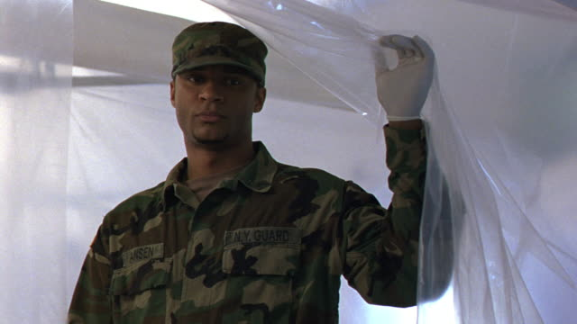 MEDIUM ANGLE OF PLASTIC SHEET. ARMY SOLDIER WITH LATEX GLOVES ON LIFTS SHEET, STARES SADLY AT WHAT HE SEES. MEDICAL CENTERS.
