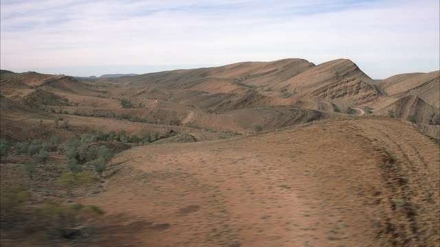 AERIAL OVER ROLLING DIRT HILLS. SEE BLUE SKY STREAKED WITH WISPY WHITE CLOUDS. DRY GREEN FOLIAGE SPOTTING THE DIRT HILLS.