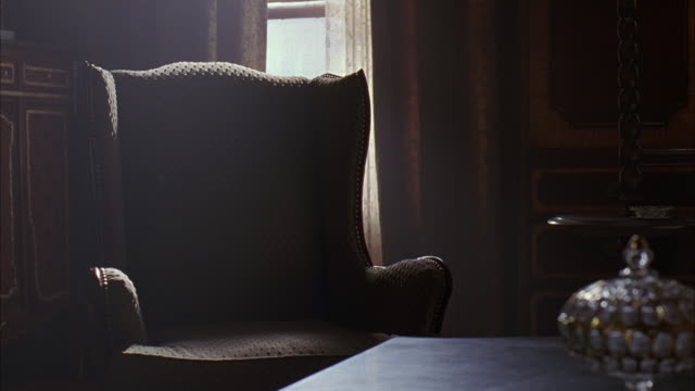CLOSE ANGLE ON AN ARM CHAIR IN A HOME INTERIOR, MAYBE AN OFFICE DEN LIVING ROOM OR PARLOR.  THE WALLS COVERED  WITH WOOD PANELING, WITH MAYBE A CHEST OF DRAWERS OR CABINETS.  A SMALL GLASS LAMP IN THE FOREGROUND. HOME OFFICES.