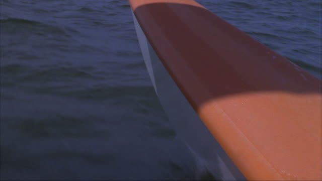 MEDIUM ANGLE HIGH ANGLE DOWN OF WATER SURFACE OF LAKE OR BODY OF WATER, MOVING POV ON SAILBOAT. SEE ORANGE SAILBOAT BOW ON RIGHT BACKGROUND.