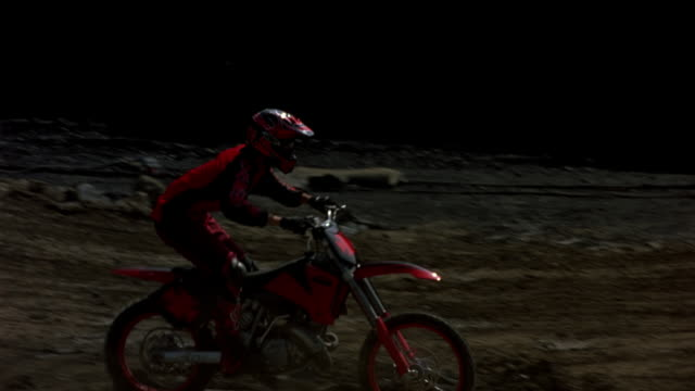 MEDIUM ANGLE OF GROUP OF DIRT BIKERS RACING ON TRACK. PANS LEFT TO RIGHT FOLLOWING BIKERS. FOCUS ON BIKER IN RED AND BLACK. BIKER MAKES A U-TURN BACK LEFT AND JUMPS OFF HILLS. PANS LEFT TO FOLLOW BIKERS JUMPING OFF HILL AND OUT OF SHOT.