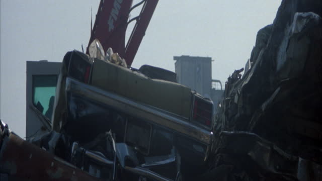 MEDIUM ANGLE OF CRANE TRUCK IN JUNKYARD OR SCRAP YARD. SEE PILE OF METAL. SEE BEAT UP BUS IN FRONT OF TRUCK. CRANE MOVING SOMETHING NOT VISIBLE IN FRAME.