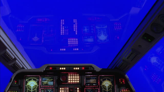 MEDIUM ANGLE OF INTERIOR OF AIRPLANE OR JET COCKPIT. SEE LIGHTS, GAUGES, BUTTONS, AND DIGITAL DISPLAYS IN ONE-PERSON COCKPIT. SEE SOLID BLUE SCREEN OUTSIDE OF COCKPIT WINDOWS.