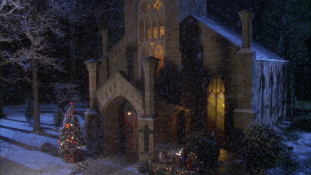 ZOOM IN OF HISTORIC STYLE CHURCH WITH LIGHTS ON AND CHRISTMAS TREE AND LIGHTS IN FRONT. IT IS SNOWING, AND SOME SNOW ON GROUND. ZOOMS IN TO DOOR OR ENTRANCE OF CHURCH AND NATIVITY SCENE, DURING CHRISTMAS SEASON.