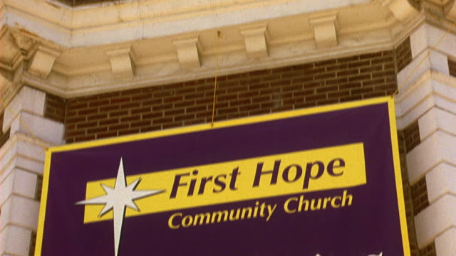 PAN DOWN FROM CRUCIFIX ON CORNER OF BRICK AND STONE BUILDING TO BANNER THAT READS FIRST HOPE COMMUNITY CHURCH WHERE HOPE IS A WORK IN PROGRESS. PAN DOWN FURTHER TO ENTRANCE DOOR AND PEDIMENT THAT READS FIRST HOPE COMMUNITY CHURCH, ALL ARE WELCOME.