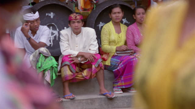 MEDIUM ANGLE OF PEOPLE SITTING ON STONE STEPS LOOKING TOWARDS CAMERA. TWO MEN ON LEFT WEARING WHITE SHIRTS, MULTI-COLORED PANTS, AND HEADDRESSES.