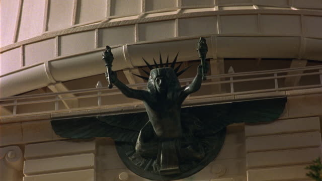 MEDIUM ANGLE OF BRONZE SCULPTURE OVER ENTRANCE TO PLANETARIUM OR MUSEUM. SCULPTURE OF MAN WITH SPIKED CROWN HOLDING A TORCH IN EACH HAND. BUILDING IN NEOCLASSICAL STYLE. MINIATURE MODELS. OBSERVATORIES.