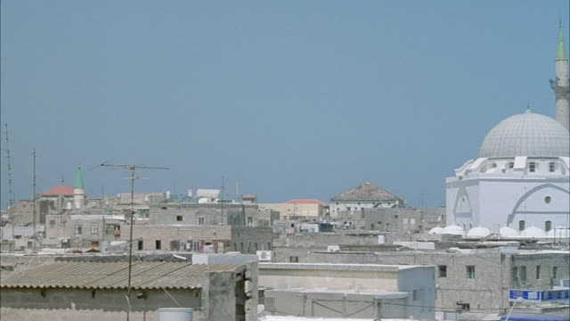 MEDIUM ANGLE PAN LEFT OF TOWN IN MIDDLE EASTERN COUNTRY. WHITE MOSQUE WITH TOWER SPIRE ON RIGHT. MIDDLE EAST.