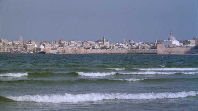 WIDE ANGLE OF OCEAN WITH WAVES BREAKING RIGHT IN FOREGROUND. MIDDLE EASTERN TOWN WITH MOSQUES AND SPIRES IN FAR BACKGROUND. MIDDLE EAST.