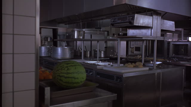 WIDE ANGLE OF HOTEL KITCHEN FACILITY. POTATOES ON CUTTING BOARD. WATERMELON AND OTHER FOOD IN FOREGROUND. COUNTER TOPS AND OVENS.