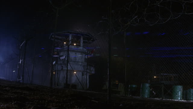 WIDE ANGLE OF GUARD TOWER BEHIND CHAIN LINK FENCE WITH RAZOR WIRE ON TOP. COULD BE USED FOR MILITARY BASE, PRISON CAMP OR NORTH KOREAN DMZ. INTERNATIONAL BORDERS.