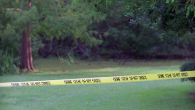 MEDIUM ANGLE OF CRIME SCENE DO NOT CROSS POLICE TAPE TIED TO TREE IN FRONT YARD OR LAWN. CRIME SCENES AND EMERGENCIES.