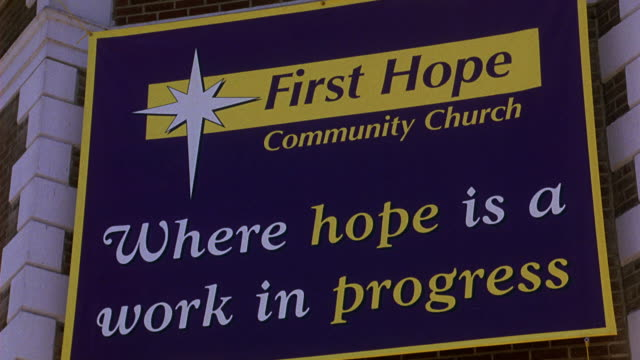 PAN DOWN FROM CRUCIFIX ON CORNER OF BRICK AND STONE BUILDING TO BANNER THAT READS FIRST HOPE COMMUNITY CHURCH WHERE HOPE IS A WORK IN PROGRESS.