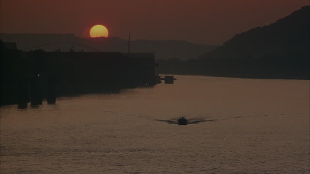 MEDIUM ANGLE LOOKING DOWN RIVER FROM BRIDGE. SEE SUN SETTING OVER HILLS IN BACKGROUND. SEE SMALL BOAT IN WATER MOVING TOWARD POV. BOAT DOES U TURN AND MOVES AWAY FROM CAMERA. SEE LIGHT FILTER CHANGE MIDWAY THROUGH SHOT.