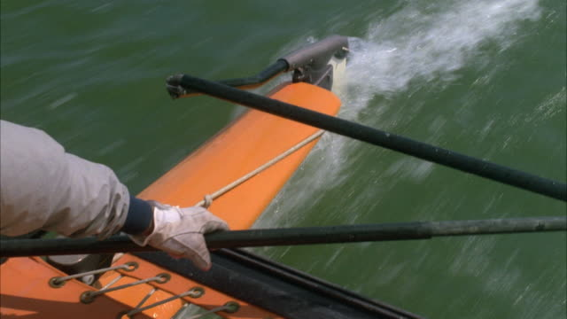 CLOSE ANGLE LOOKING DOWN ON MAN'S ARM CONTROLLING TILLER ON CATAMARAN OR SAILBOAT. SEE WATER PASSING BY HULL AND RUDDER IN BACKGROUND. MAN HAS ON GLOVE AND JACKET.