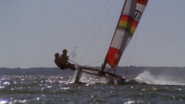 MEDIUM ANGLE OF A SAILBOAT WITH ORANGE AND WHITE SAILS PASSING BY. SEE TWO PEOPLE PULLING ON FORESTAYS OF SAIL TO KEEP BOAT FROM TIPPING. SEE OTHER SAILBOATS IN BACKGROUND. COULD BE A RACE.