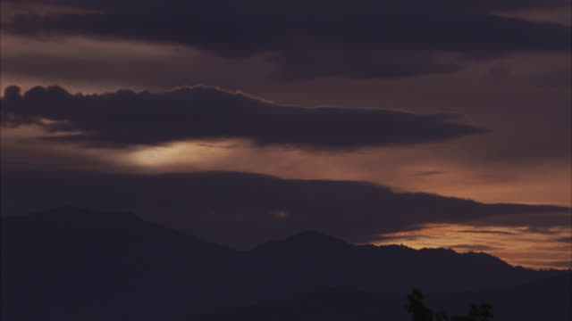 WIDE ANGLE OF MOUNTAIN SKYLINE AT DUSK. SKY IS ORANGE AND GREY WITH DARK THIN CLOUDS. SEE MOUNTAINS IN BACKGROUND.