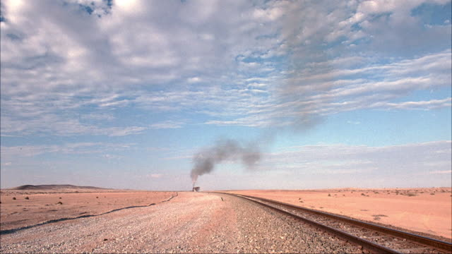 MEDIUM ANGLE OF DESERT TRAIN TRACKS AND STEAM ENGINE TRAIN. SEE STEAM ENGINE TRAIN MOVE AWAY FROM CAMERA ON TRACKS AND DISAPPEAR IN HORIZON.