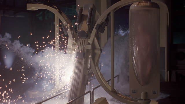 MEDIUM ANGLE OF FUTURISTIC MACHINE IN WAREHOUSE OR BASEMENT ROOM. SEE SPARKS AND SMALL EXPLOSIONS FROM MACHINE. SEE SMOKE FROM MACHINE.