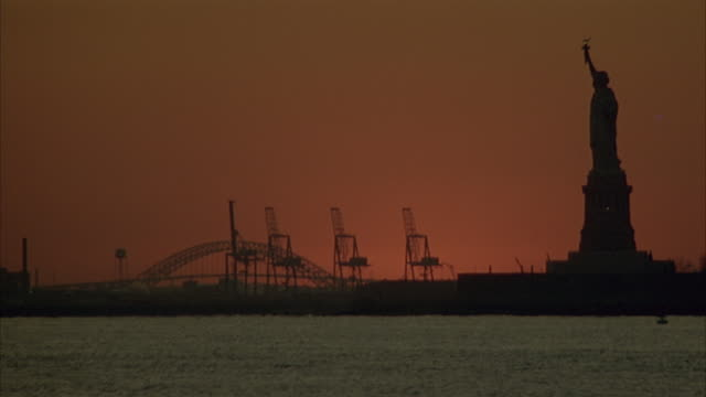 WIDE ANGLE OF SILHOUETTE OF STATUE OF LIBERTY ON RIGHT AND POWER LINES IN FAR BACKGROUND. RIVER OR BODY OF WATER IN FOREGROUND. SKY HAS TINT OF ORANGE. BEAUTY SHOT.