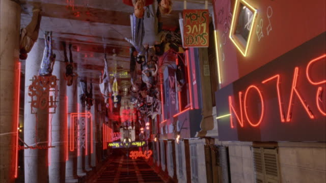 MEDIUM ANGLE OF RED LIGHT DISTRICT AREA. SEE START OF SHOT UPSIDE DOWN UNTIL CAMERA ROTATES. THEN SEE SEVERAL PEOPLE DRESSED UP IN UNUSUAL OUTFITS AND COSTUMES. SEE EROTIC SIGN IN BACKGROUND.