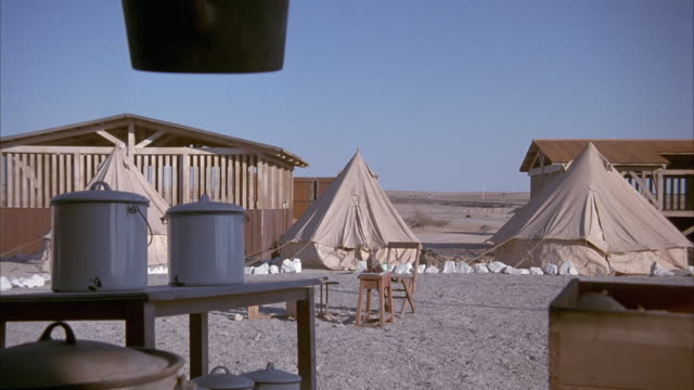 MEDIUM ANGLE OF THREE TENTS AT MINING CAMP WITH DINING TABLE WITH CANISTERS IN FOREGROUND. SEE WOODEN FRAME OF SHACKS OR BUILDINGS IN BACKGROUND. SEE EXPLOSIONS OF TENTS AND WOODEN SHACKS, FOLLOWED BY FIRE AND BLACK SMOKE, IN BACKGROUND.