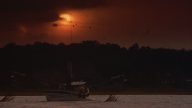MEDIUM ANGLE OF FISHING BOAT WITH NETS ON BOTH SIDES MOVING IN WATER, POSSIBLY RIVER OR LAKE. ORANGE SUN IN BACKGROUND.