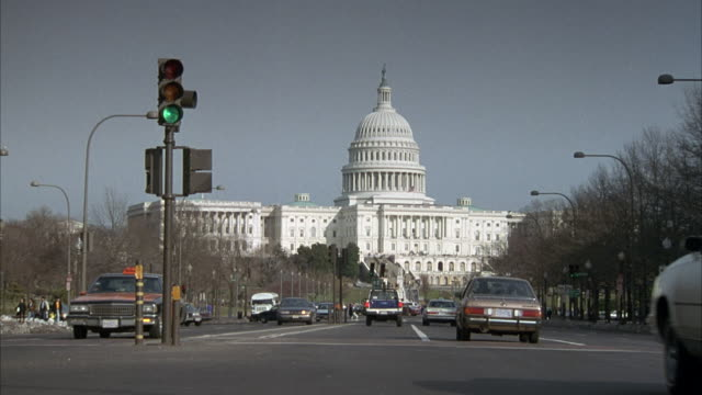 MEDIUM ANGLE OF CAPITOL BUILDING IN CENTER BACKGROUND, CITY STREET IN FOREGROUND. ORANGE TAXI APPROACHES FRONT AND TURNS RIGHT.
