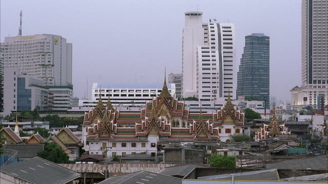 MEDIUM ANGLE ESTABLISH OF CITY. SEE ORANGE, GREEN, RED AND WHITE OF TEMPLE OR PALACE. SEE HIGH RISE BUILDINGS IN BACKGROUND. SEE URBAN AREA IN FRONT OF PALACE.