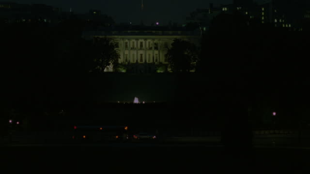 ESTABLISHED WIDE ANGLE OF WHITE HOUSE LIT AT NIGHT. FRONT YARD AND TREES SURROUND WHITE HOUSE. SEE LIGHTS ON TOP OF GATE AND SOME TRAFFIC IN FOREGROUND. OBSCURED BUILDINGS IN BACKGROUND.