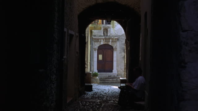 WIDE ANGLE OF WOMAN SITTING IN NARROW ALLEY IN EUROPE. WOOD DOOR VISIBLE IN BACKGROUND. MAN WALKS INTO ALLEY.