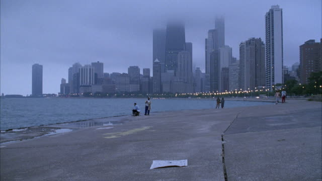 WIDE ANGLE OF BEACH ALONG LAKE MICHIGAN AND SKYSCRAPERS IN BACKGROUND. HEAVY, LOW CLOUDS OBSCURE VIEW OF SKYSCRAPERS.