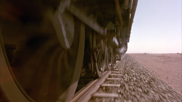 MEDIUM ANGLE OF WHEELS OF STEEL STEAM ENGINE TRAIN AS IT CHUGS THROUGH THE DESERT. SEE GEARS ON WHEELS TURNING. TRACKS ARE LAID ON TOP OF GRAVEL. STEAM DRIFTS DOWN FROM BOTTOM OF THE TRAIN.