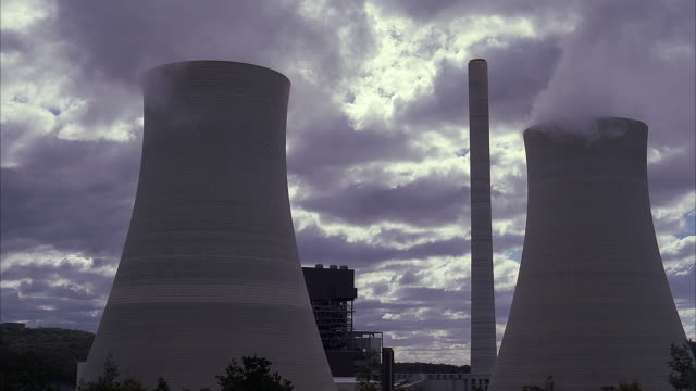WIDE ANGLE OF NUCLEAR POWER PLANT. SEE PAIR OF CONCRETE COOLING TOWERS WITH STEAM RISING FROM TOP. TALL NARROW SMOKESTACK STANDS IN BETWEEN. GRAY CLOUD DARKENED SKY.