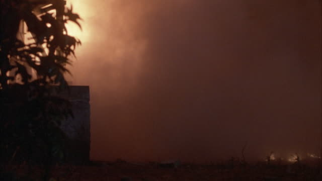 MEDIUM ANGLE OF BRICK SHACK. SEE CLOSE ANGLE OF TREE, LIT LAMP NEXT TO DOORWAY OF SHACK. SEE FIRE EXPLOSIONS FROM BEHIND, THEN ENTIRE SHACK BLOWS UP INTO FLAMES AND SMOKE.