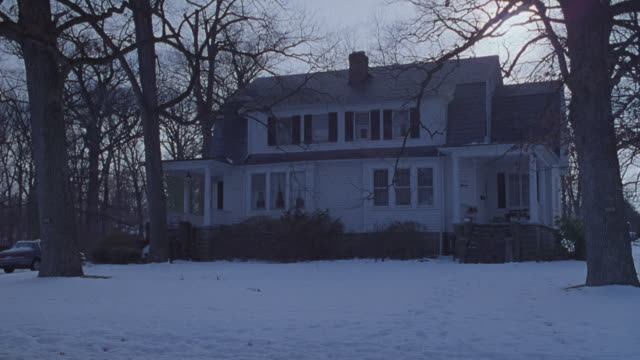 MEDIUM ANGLE OF TWO STORY HOUSE. CAR PARKED AT LEFT BEHIND TREE, SNOW ON GROUND, WINTER.