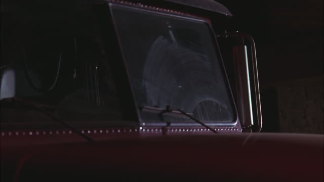 MEDIUM ANGLE OF HOOD AND WINDSHIELD TO BIG RIG OR SEMI TRUCK. WINDSHIELD WIPERS VISIBLE.