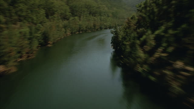 AERIAL OVER DENSELY TREE COVERED MOUNTAINS. SEE POV FLY ALONG RIVER. SEE POV FLY OVER MOTORBOAT ON RIVER SPEEDING AWAY FROM POV. SEE POV RISE TO VIEW MOUNTAINTOPS. SEE CLEAR BLUE SKY.