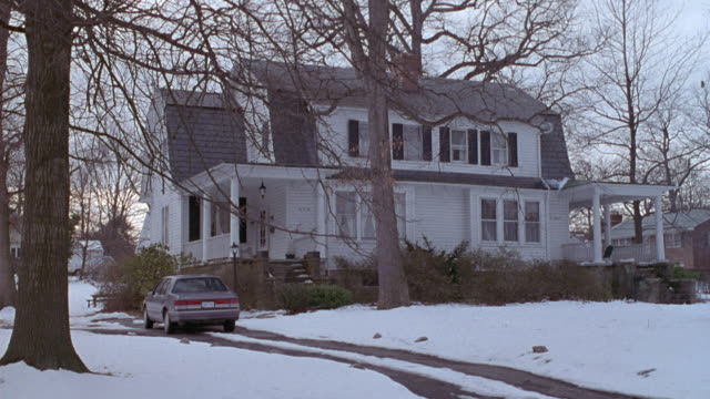 MEDIUM ANGLE OF WHITE TWO STORY COTTAGE STYLE HOUSE WITH FRONT YARD BLANKETED WITH SNOW. SEE BARE TREES AND SEE TAN SEDAN PARKED AT LEFT.