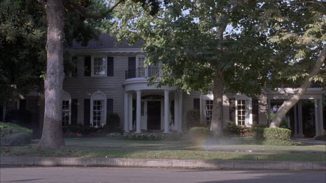MEDIUM ANGLE OF TWO STORY HOUSE PARTIALLY BLOCKED BY TREES IN FRONT YARD. SEE SPRINKLERS SPRAYING WATER AS PAPERBOY RIDES BY ON BICYCLE AND THROWS NEWSPAPER ONTO LAWN. UPPER CLASS.