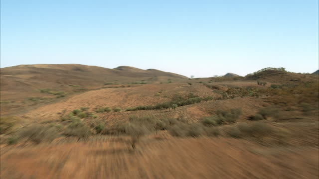 FAST FRONT MOVING AERIAL THROUGH VALLEYS AND PLAINS OF DESERT MOUNTAINS OR HILLS. SOME SHRUBS ON HILLS AND PLAINS.