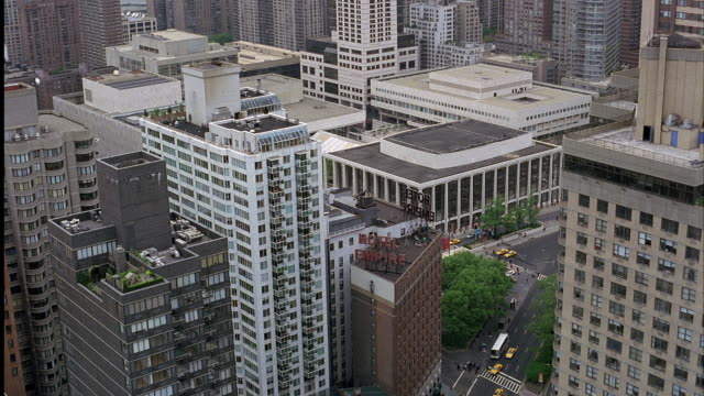 AERIAL, HIGH ANGLE DOWN OF CITY STREET AND BUILDINGS. SEE HOTEL EMPIRE ON STREET. PANS UP. UPPER WEST SIDE MANHATTAN NEAR LINCOLN CENTER AND JUILLIARD SCHOOL. HIGH RISE BUILDINGS VISIBLE, HARLEM RIVER IN BACKGROUND.