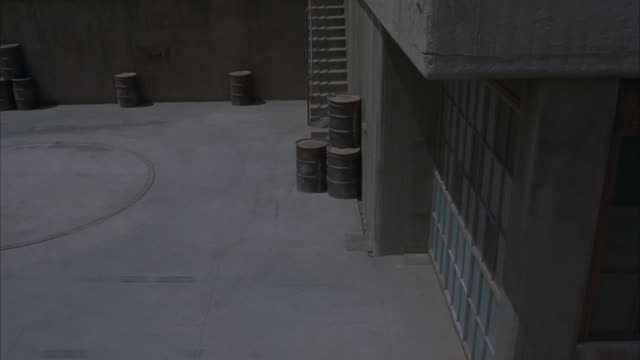 HIGH ANGLE DOWN OF VAN CRASHING THROUGH WOODEN DOOR AND GLASS FROM INSIDE TO OUTSIDE. SEE GASOLINE CANS STACKED ON OUTSIDE OF WAREHOUSE. CAR STUNT.