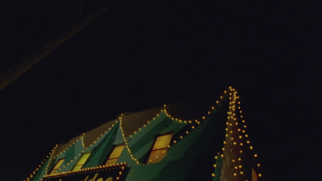 UP ANGLE OF SIDE VIEW OF BIG TOP VIDEO STORE. TWO STORY BRICK BUILDING HAS PAINTED CIRCUS TENT IN BRIGHT BLUE COLORS ON FRONT.