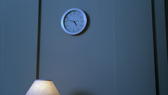 MEDIUM ANGLE OF CLOCK ON WALL IN HOTEL LOBBY. CLOCK HAS MODERN DESIGN AND TIME IS 5:47. SEE LAMP SHADE ON BOTTOM.