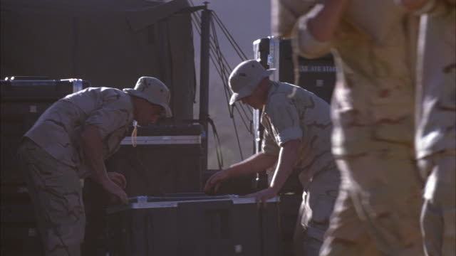 CLOSE ANGLE OF U.S. MILITARY VEHICLE IN DESERT. SEE VEHICLES MOVE AND SOLDIERS PACKING CONTAINERS. SEE SOLDIERS ENTERING VEHICLE. COULD BE MILITARY BASE OR CAMP.