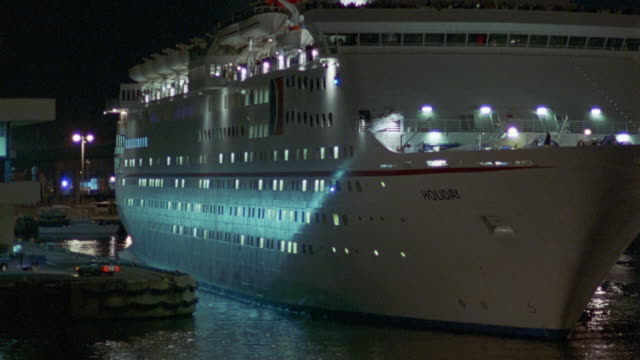 WIDE ANGLE PANNING LEFT TO RIGHT ACROSS FRONT OF LARGE WHITE CRUISE SHIP CALLED HOLIDAY AT NIGHT. SEE LIGHTS ON IN CABINS. PEOPLE SILHOUETTED ALONG BALCONY. SMOKE OR STEAM COMING OUT OF RED CHIMNEY ON TOP OF BOAT.