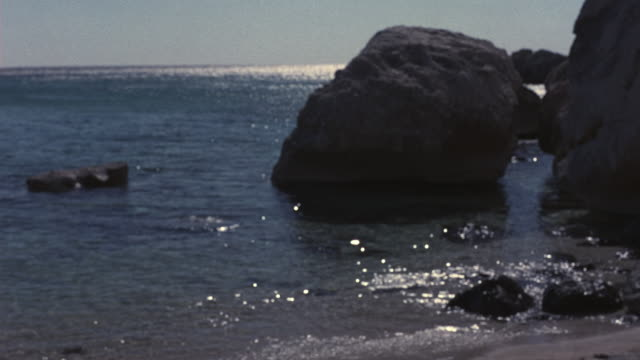 MEDIUM ANGLE OF CLEAR BLUE WATER OF OCEAN WAVES ROLLING ONTO BEACH. SEE LARGE BROWN BOULDERS IN BACKGROUND. SEE ARM OF MAN HOLDING SNORKELING GOGGLES AND BROWN WOODEN POLE FRAME RIGHT.
